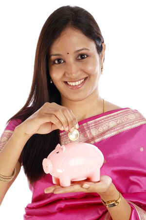 Young Indian traditional woman with a piggy bank over white background  photo