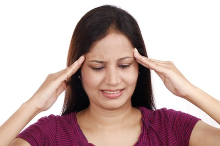 Young Indian female teenager with headache against white background photo