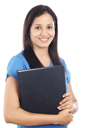 Young female Indian student with books against white background photo
