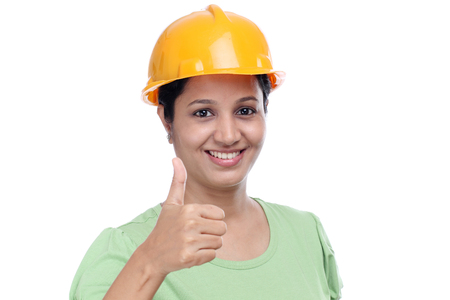 Smiling female architect with thumbs up gesture against white photo