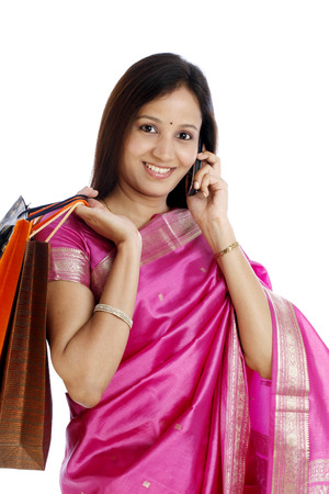 indian saree: Young Indian traditional woman with shopping bags and talking on cellphone