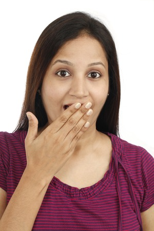 inhibited: Young woman with hand over mouth against white background