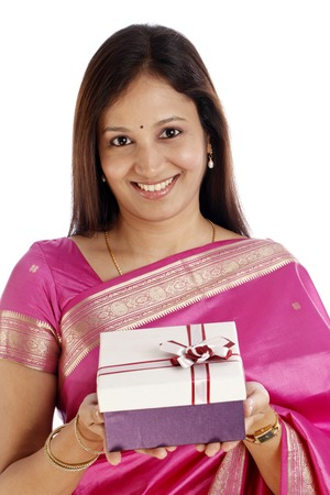 Smiling young Indian traditional woman holding gift box in hands on white background  photo