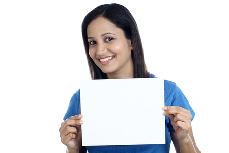 Excited young woman showing blank white card against white photo