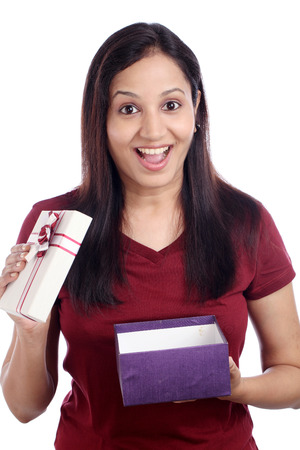Excited young woman with gift box against white photo