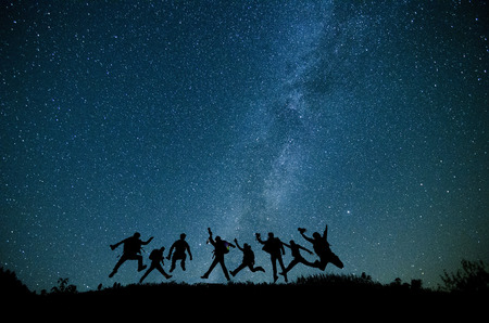 Happy young friends jumping under starry sky, night sky with amazing stars. photo