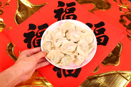 chinese new year food: Chinese dumplings- Jiaozi, new year food, spring festival food on traditional spring festival couplets background