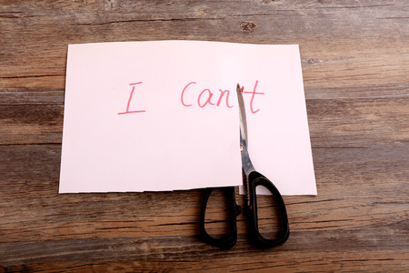 i t: cutting the letter T of the written word I cant to I can Stock Photo