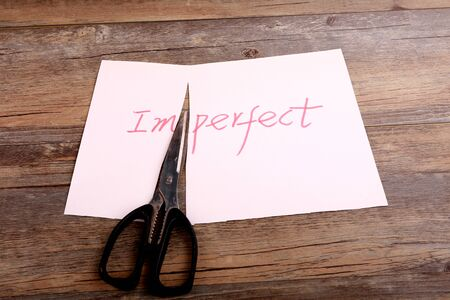 imperfect: A scissor cuts perfect from imperfect on the desk. Stock Photo