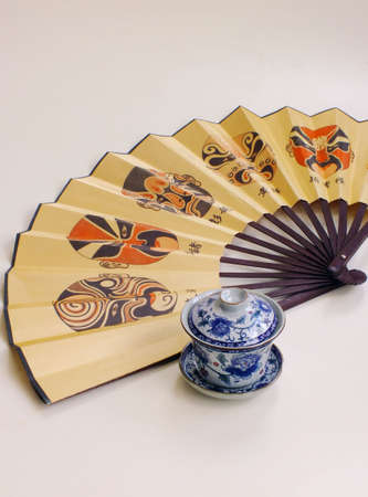 paper fan: chinese paper fan and a cup of tea on white background
