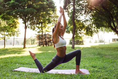 Yoga is her strength. Full length side view of young beautiful fit woman in sportswear doing yoga in green park