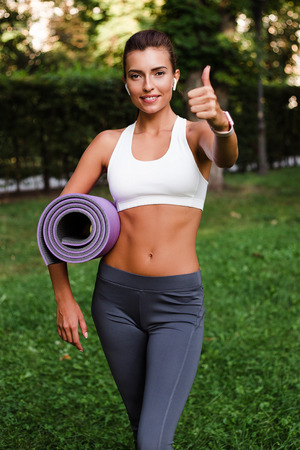 Sport is her lifestyle. Young beautiful fit woman in sportswear holding yoga mat and looking at camera with smile in green park