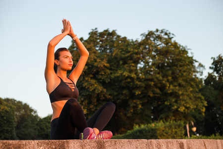 Yoga with joy. Young beautiful fit woman in sportswear doing yoga while sitting in the park