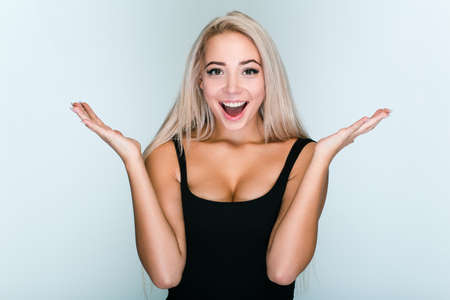 Have you seen it? Beautiful young woman with blond hair looking excited while standing against grey background