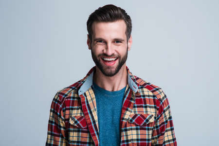 Best smile you ever saw. Portrait of handsome young man looking at camera with smile while standing against white background