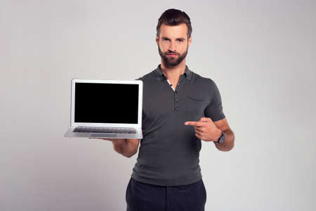 Your new device. Handsome young man looking at camera and pointing at his laptop while standing against white background