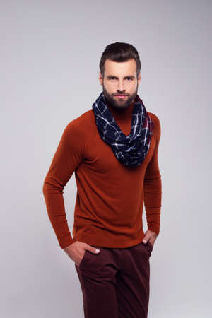 His look for next autumn. Handsome young man in scarf looking at camera while standing against white background