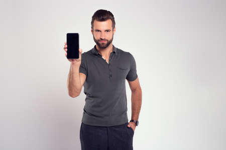 Your new phone! Handsome young man looking at camera and showing his mobile phone while standing against white background
