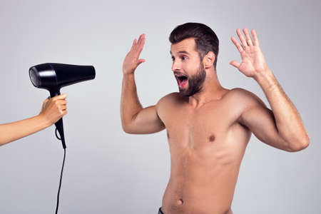 I give up! Handsome shirtless young man keeping hands up and looking at hairdryer while standing against white background