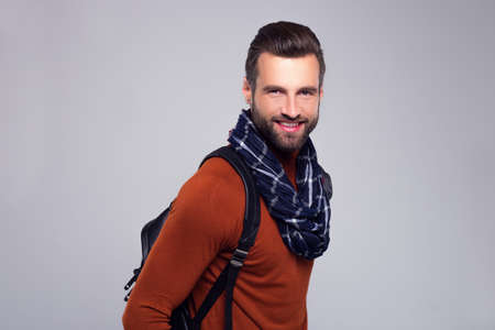 Ready to visit new city. Handsome young man in scarf looking at camera with smile while standing against white background