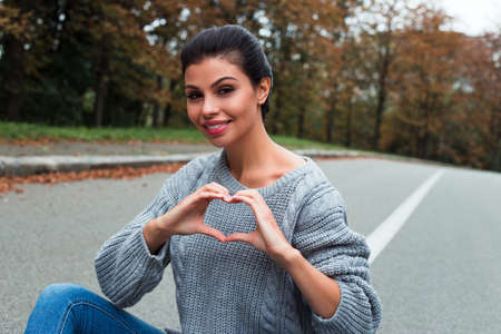 Love from a beauty. Beautiful young woman in sweater looking at camera with smile while sitting outdoors.