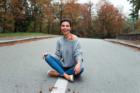 Candid and cozy. Beautiful young woman in sweater looking at camera with smile while sitting outdoors.