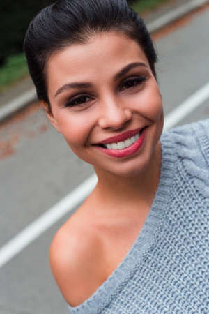 Portrait of beauty. Beautiful young woman in sweater looking at camera with smile while standing outdoors. Banco de Imagens