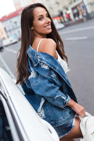 Peace in her smile! Beautiful young woman in jeans jacket looking away with smile while standing outdoors