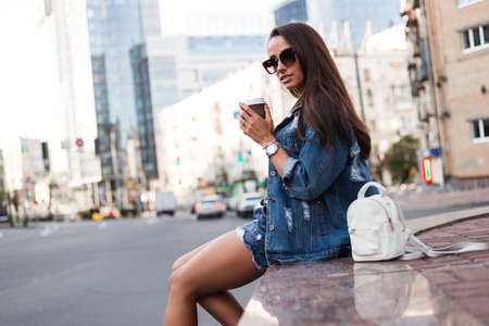 Coffee brake in the city. Beautiful young woman in jeans jacket holding coffee cup and looking away while sitting outdoors