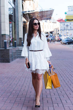 Where can I buy new shoes? Full length of beautiful young woman in sunglasses holding shopping bags and looking away while walking outdoors
