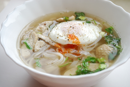 Bowl of vietnamese chicken pho with an poached egg. Pho ga with egg. Rice noodle soup.
