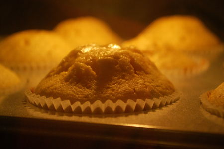 Baking vanilla muffins in the hot oven. Dough rising.