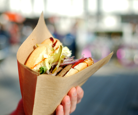 Hands holding wrapped in paper burger on city background. Stock Photo