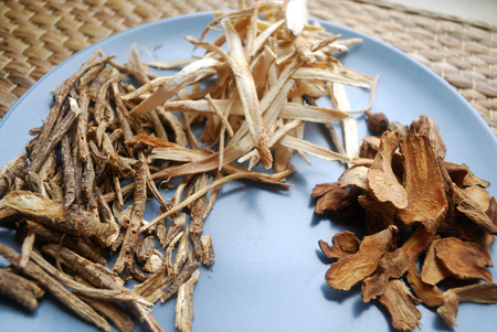 Assorted chinese traditional medicine herbs on a plate. Fang feng, bai zhu, huang qi roots sliced ??and dried.