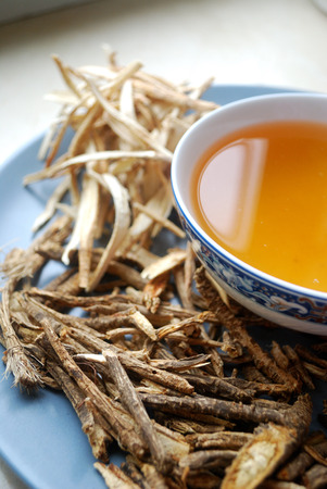 Bowl of chinese herb tea with dried assorted roots.