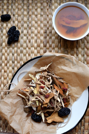 Chinese traditional medicine script. Herbal tea with jujubes, goji berries, gingseng.