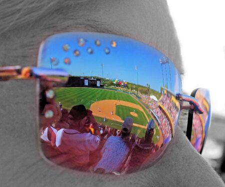 A baseball game reflected in the sunglasses.