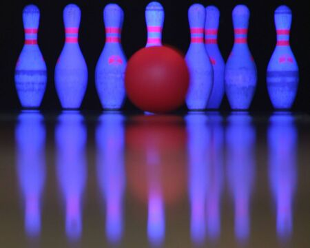 A bowling ball just about to hit the pins.
