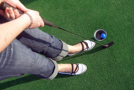 Putting a ball at an adventure golf. Stock Photo