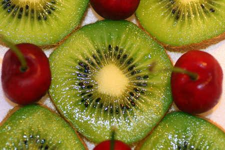 A macro of some kiwi and cherries.