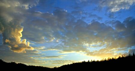 A sunset with great clouds and a silhouette of trees. Stock fotó