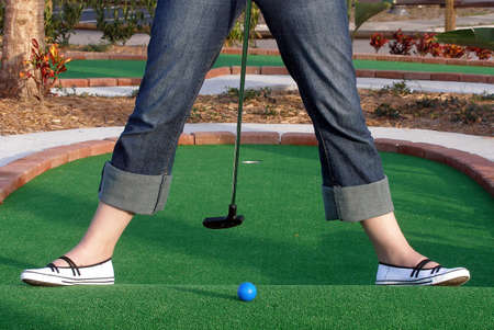 Playing Adventure Golf, downhill shot, ball, club and hole. Stock Photo
