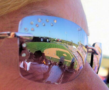 Ball Game and crowd reflection in a womans sunglasses.