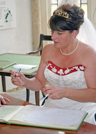 A Bride signing the register after her wedding. photo