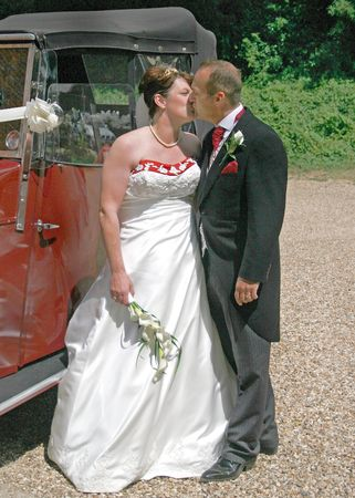 Bride and Groom Kissing in front of their Wedding Car photo