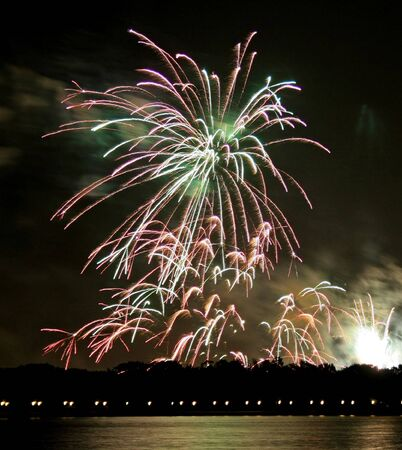 Fireworks in the dark sky over a lake.