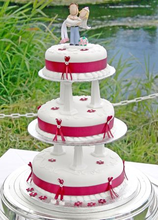Wedding Cake with Bride and Groom and lake behind. photo