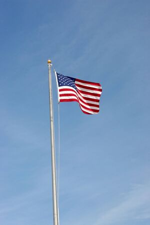 An American Flag flying in the air up a pole photo