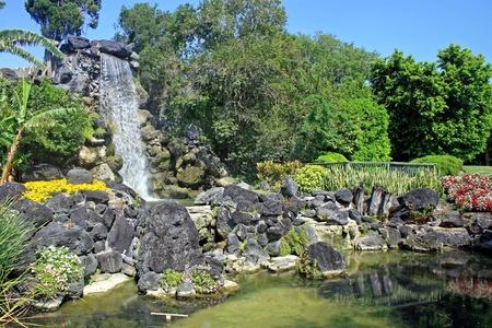 정원에있는 폭포와 커다란 바위 특징 스톡 콘텐츠