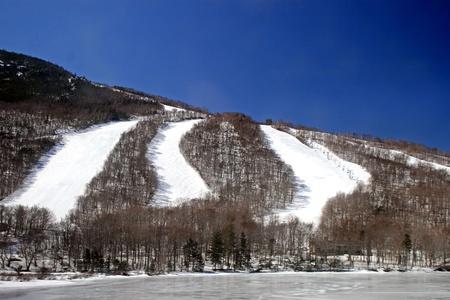 ski slopes: Molte piste da sci in inverno con lago ghiacciato a fondo Archivio Fotografico